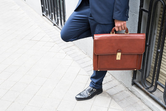 Anonymous man wearing elegant suit and holding brown leather briefcase standing at street.