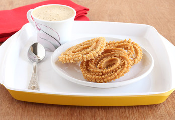 Homemade Indian snack chakli, also known as murrukku, a traditional and popular food, and coffee.