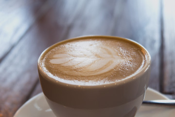 close up of a cup of coffee latte on wooden table in coffee shop.