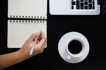 Coffee cup and laptop with writing note on the black table
