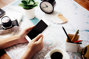 Holding mobile phone on the map to prepare traveling