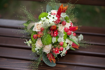 Flowers, foliage and berries in a round in a tasteful bridal floral arrangement resting on a wooden bench with blurred background. Bride's bouquet for the wedding day.