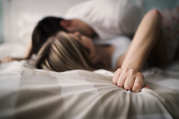 Beautiful couple being romantic and passionate in bed