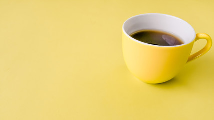 A coffee mug yellow on pastel yellow colors table .for copy space for text or Use of photo card background and Insert into message.