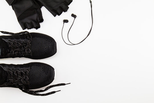 Black sport shoes, glove and headphone on white background, sport exercise concept