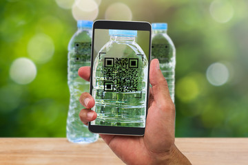 Man's hands holding smartphone scanning QR code on drinking water bottle in the garden, business concept