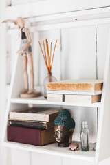 White wooden shelf with different old books and statue of Buddha. Cozy light interior rustic style