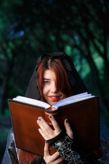 Picture of witch in cloak with book