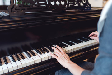 Girl playing on black piano