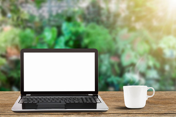 Laptop with blank white screen and hot coffee cup on vintage wooden table on blurred garden background