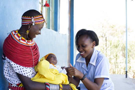 Nurse examing Mother and Baby in clinic. Kenya, Africa.