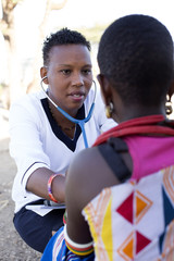 Nurse examing female patient in rural village. Kenya, Africa