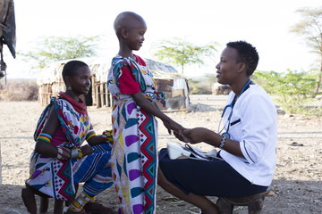 Nurse examing Mother and Daughter in Samburu village. Kenya. Africa.