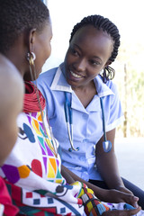 Nurse examing Mother and Daughter in clinc. Kenya, Africa.