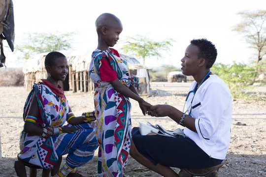 Nurse examining woman and child
