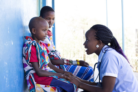 Nurse examing Mother and Daughter in clinic. Kenya, Africa.