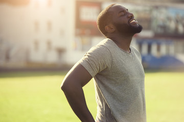 A handsome black man is feeling happy and relaxed, resting after workout in the field
