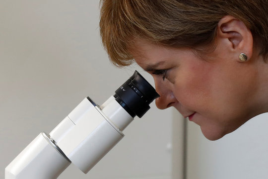 Scotland's First Minister Sturgeon takes a look through a microscope during a visit to Aquila BioMedical in Edinburgh