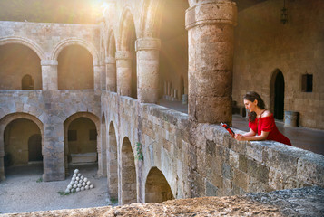 girl in red dress reading a book in the old castle