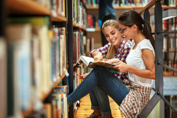Two female students read and learns by the book shelf at the library.Reading a book.