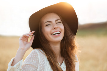 Beautiful young happy woman standing in the field