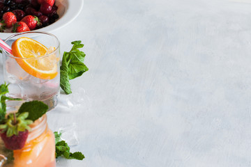 Background with fresh fruit cocktails preparing. Glass of cold drink with citrus slice, mint and ice, berries in bowl ready to use, refreshment and summer concept, close up picture with free space