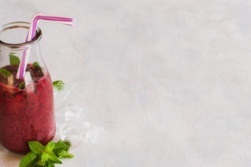 Bottle of smoothie on white background. Fruit drink from wineberry decorated mint leafs, refreshment in summer period, detox, healthy food close up picture with free space on right