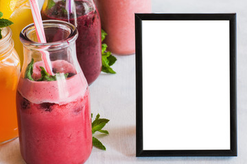 Picture frame with fresh fruit smoothies nearby. Food blogs, menu and recipes for web sites of cafe and restaurant, close up picture with copy space