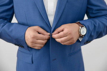 Young Caucasian male closing his jacket. Horizontal detailed close-up shot of elegant male wearing blue suit and large wristwatch getting ready.