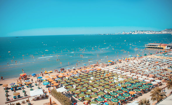 Aerial view to beach of Durres, Albania, full of umbrellas and people in summer.