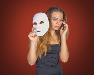 Young emotional woman holding mask in a hands pose in studio on gray background