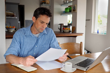 Man reading a document in home office environment
