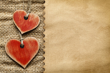 Wooden hearts and paper sheet on fabric background