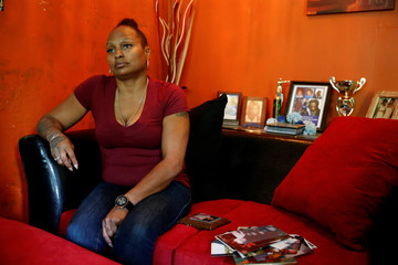 Temako McCarthy, whose son La-Reko Williams died in a Taser incident with police, sits with pictures at her home in Charlotte