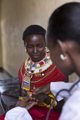 Female Doctor examining female Samburu patient. Kenya, Africa.