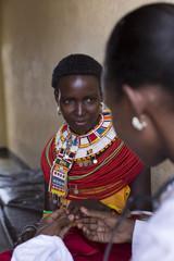 Female Doctor examing female Samburu patient. Kenya, Africa.