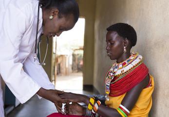 Female Doctor examining woman from Samburu tribe. Kenya, Africa.