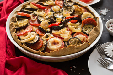 Homemade vegetable pie (galette) with grilled eggplants, tomatoes and onion on brown wooden background. Selective focus