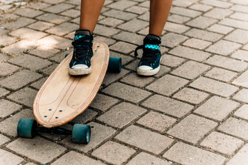 Girl's leg in sneakers standing on a skateboard.