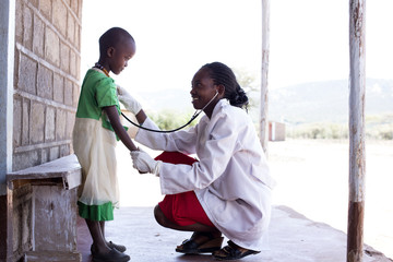 Female doctor examing child (female). Kenya, Africa.