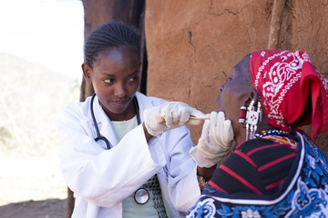 Doctor examining patient in Maasai village. Kenya, Africa