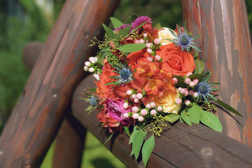 Orange hues wedding bouquet with freesias, roses and berries positioned on a rustic wooden fence, under the sunlight
