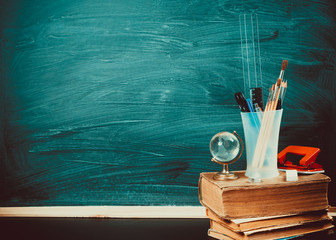 Old blackboard with chalk, books, a globe and a pencil. A beautiful backdrop for education, a free space for your text. Back to school. Shallow DOF.