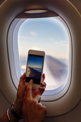 Close up of woman hands taking photo on plane.