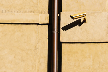 Closed circuit television (CCTV) camera on a yellow building wall.