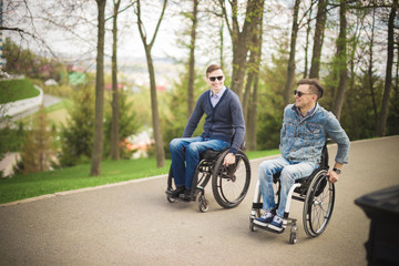 two disabled friends ride in the Park and enjoy