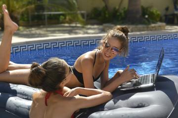 Las chicas estan en la piscina chateando y mirando las fotos en ordenador portatil