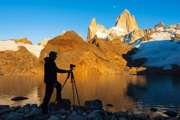 Photographer with a tripod in Lagoon de Los Tres (Laguna de Los Tres) is shooting Mount Fitz Roy massif. Los Glaciares National Park, Patagonia, El Chalten, Argentina
