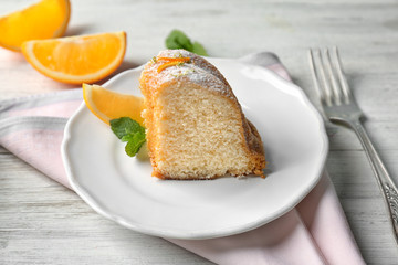 Plate with delicious citrus cake on wooden table