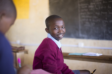 Portrait of smiling school boy in classroom. Kenya, Africa.